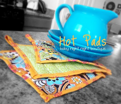 """3 hot pads next to a blue pitcher on two blue plates and titled, """" Hot Pads, baby night night boutique"""""""