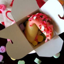A Valentine Fortune Cookie displayed in a gift box with candied hearts