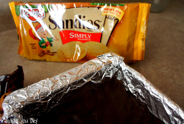 A pan with chocolate dough pressed into the bottom of it next to a package of Sandies