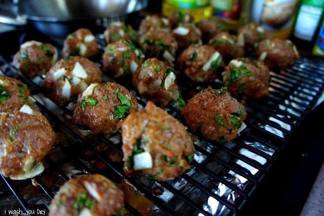 Meat balls on a rack on top of a tinfoil lined pan
