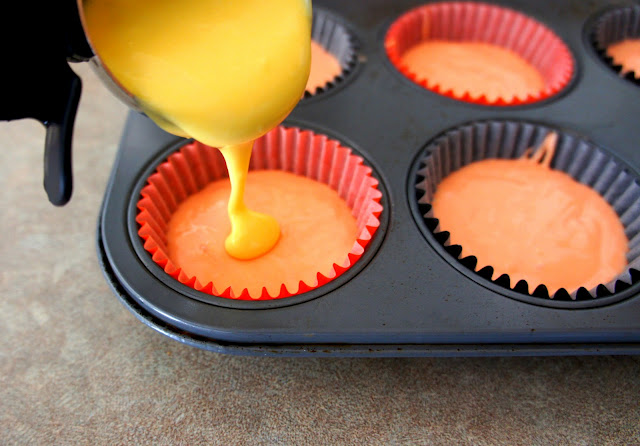 Yellow batter being poured on top of orange batter in a cupcake wrapper