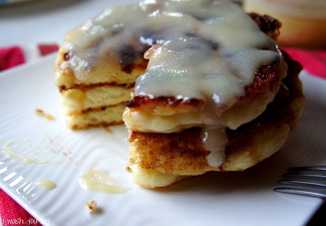 A close up of a stack of pancakes on a plate with a slice taken from it.