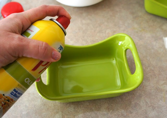 A hand spraying a baking dish with cooking spray