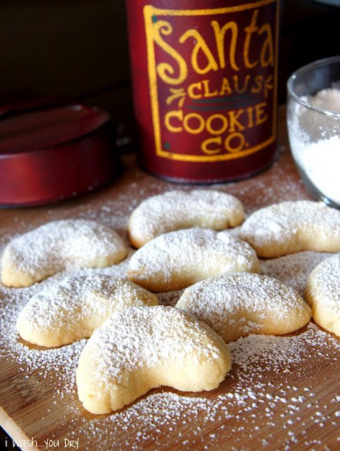 Crescent shaped cookies on a cutting board sprinkled with powdered sugar