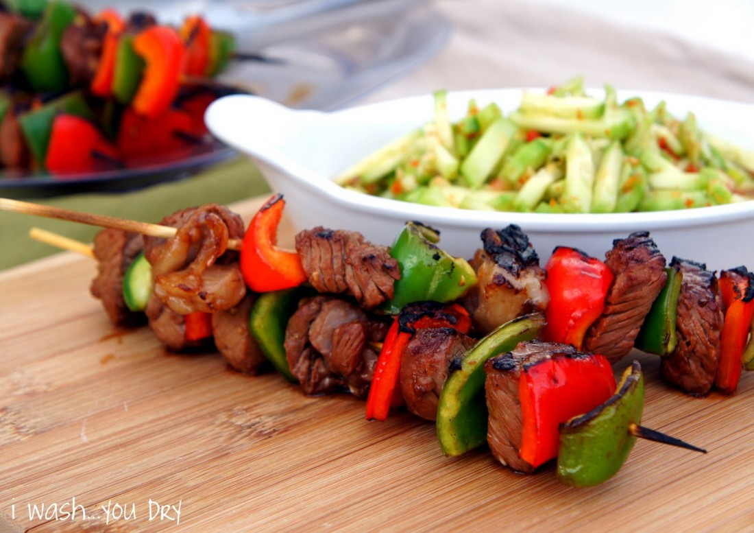 Thai beef skewers displayed on a table in front of a bowl of veggies