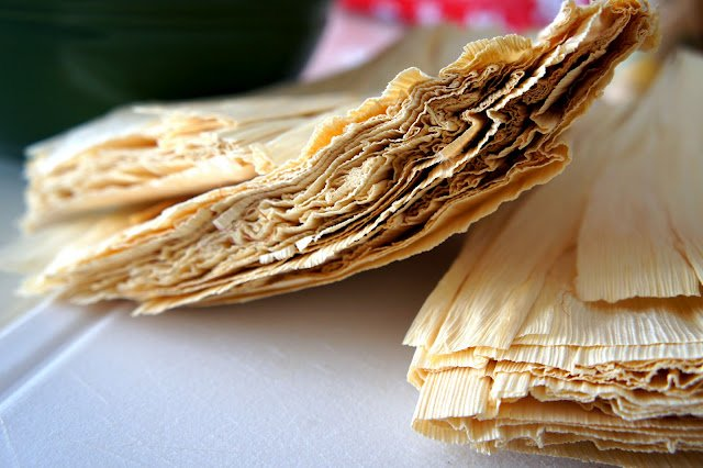 A close up of a a couple piles of dried corn husks