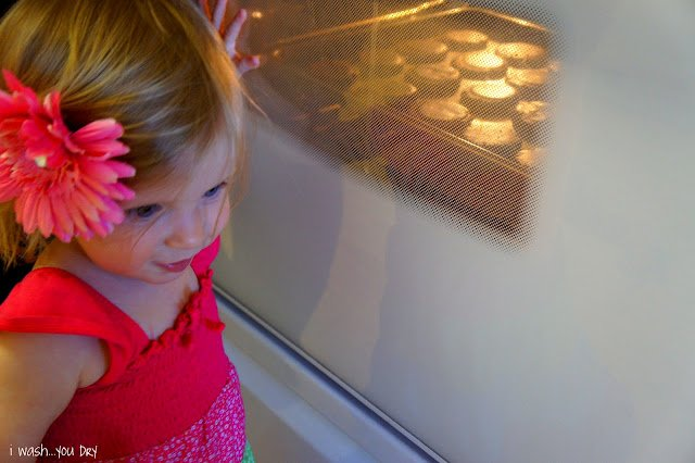 A little girl watching a pan of Nutella Peanut Butter Cookies baking in the oven.