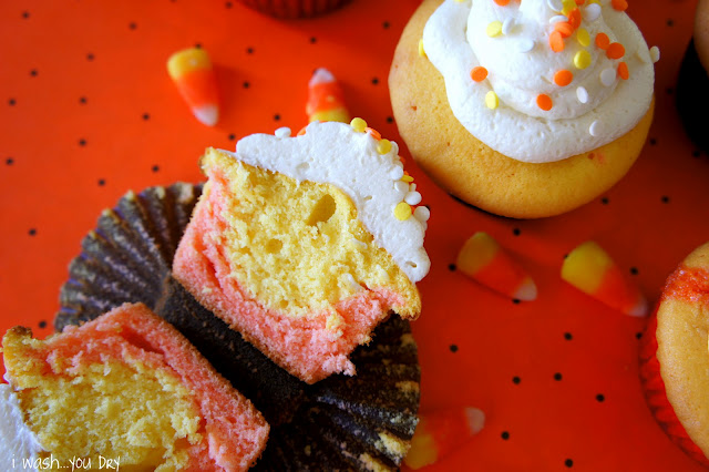Cupcakes on a table topped with white frosting and yellow, white and orange sprinkles