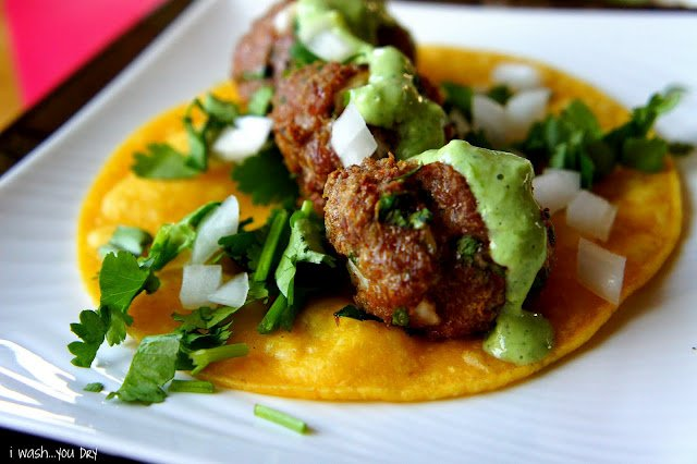 A close up of a display of Mexican Meatball Street Tacos topped with guacamole, onions and herbs