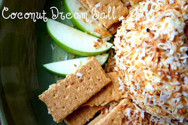 "A cream cheese ball displayed on a plate surrounded with apple slices and graham crackers titled, ""Coconut Dream Ball\"""
