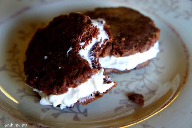 Two cookie sandwiches displayed on a plate; one with a bite taken from it