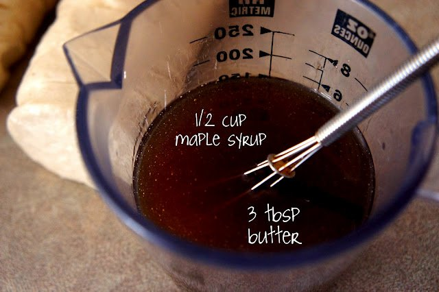 A glass measuring cup with maple syrup and butter in it