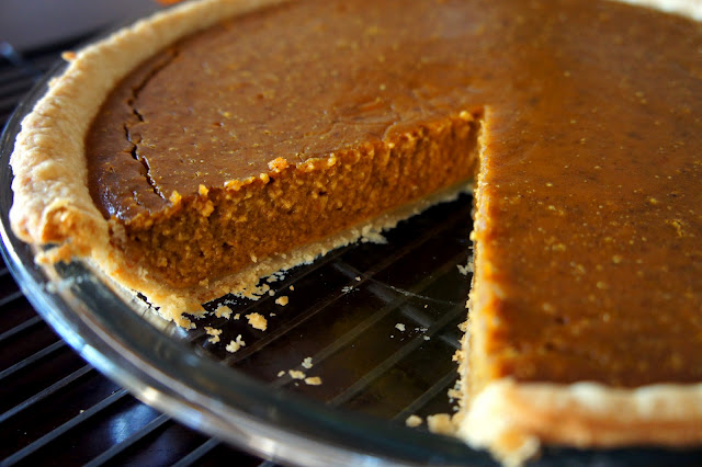 A close up of a pumpkin pie with a slice removed