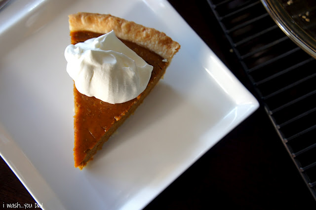 A slice of pumpkin pie on a square plate topped with a dollop of whipped cream