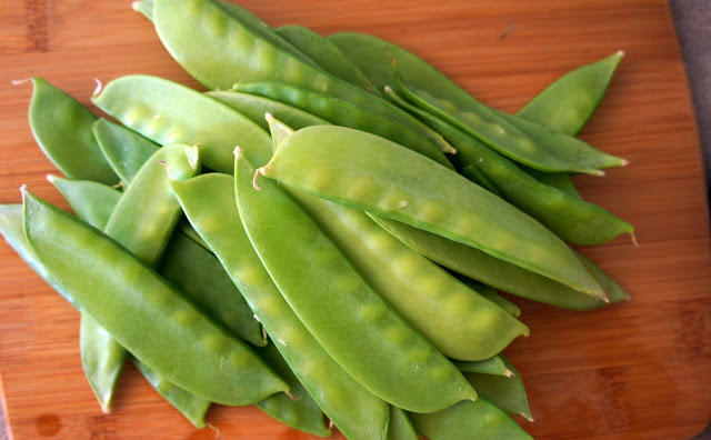 A pile of pea pods on a wooden surface
