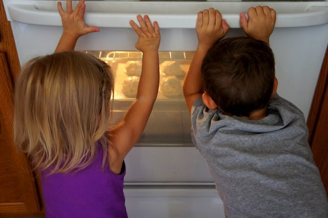 Two children watching cookies bake in an oven