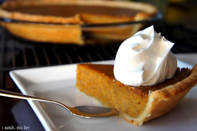A slice of pumpkin pie on a plate in front of the rest of the pie