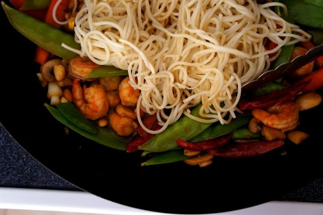 Shrimp, peas, egg noodles and other vegetables in a pan