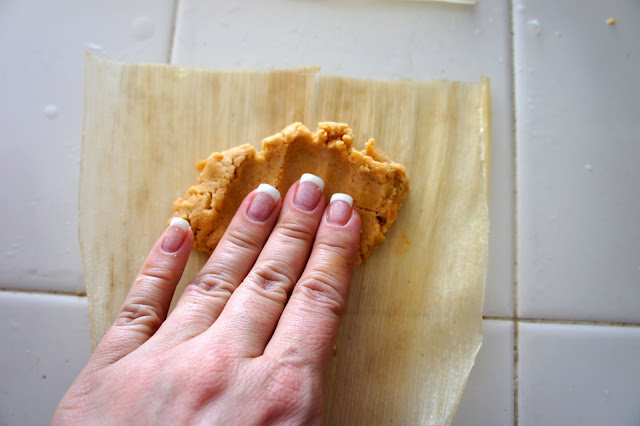 A hand pressing the tamale paste on to a corn husk