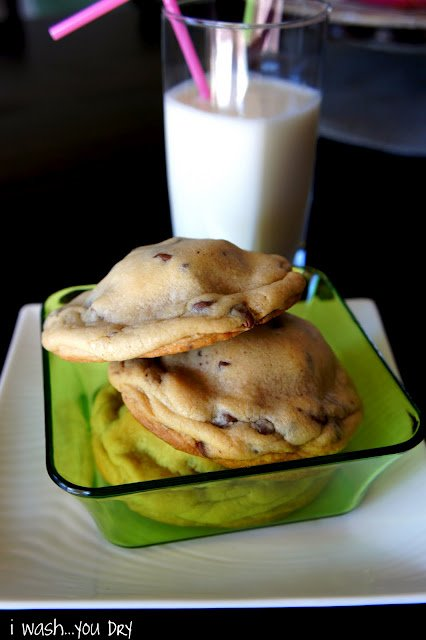 A bowl with cookies in it next to a glass of milk