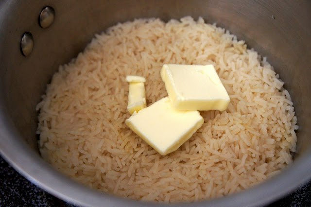 A pot of rice with 2 slices of butter on top