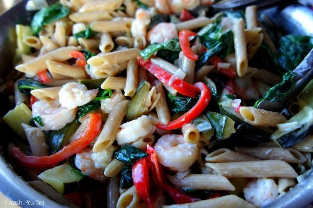 A close up of pasta, veggies, shrimp and cream sauce mixed together.