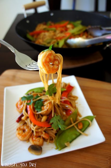 A fork holding a piece of Kung Pao Shrimp Lo Mein above the rest of the dish on a plate