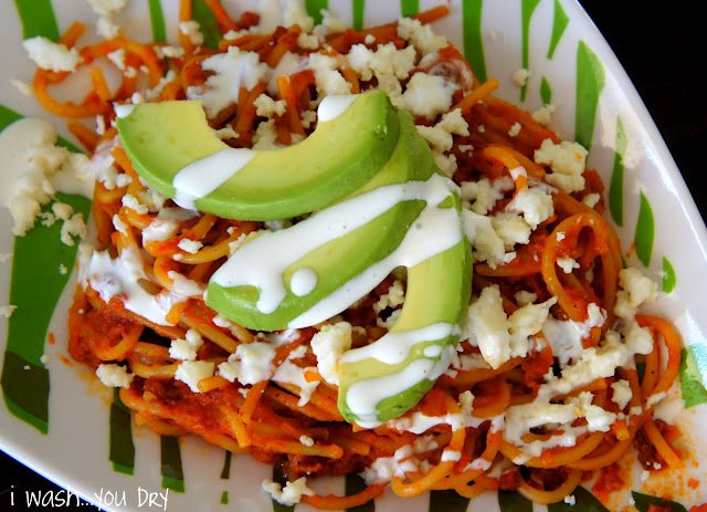 Close up of a dish of Mexican Pasta with Chorizo topped with avocado slices and drizzled with a white sauce