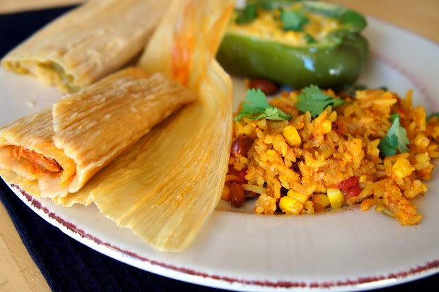 A close up a tamale on a plate with rice and a half stuffed pepper
