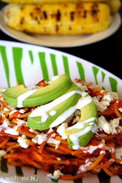 Close up of avocado slices on top of Mexican Pasta with Chorizo topped with a white sauce and cheese
