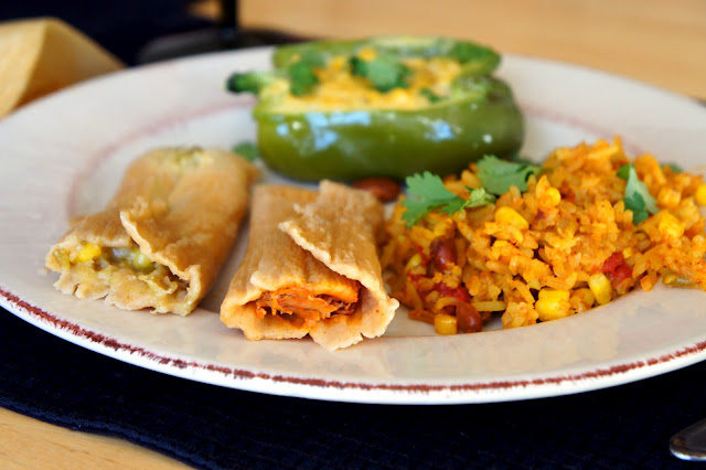 Two tamales on a plate with a side of rice and a stuffed pepper