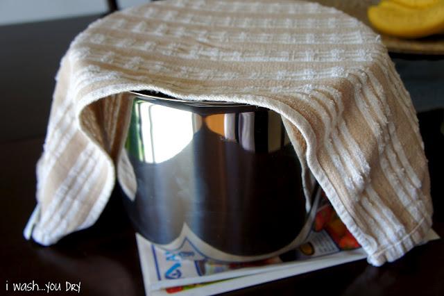 A towel over a pot of rising cinnamon roll dough