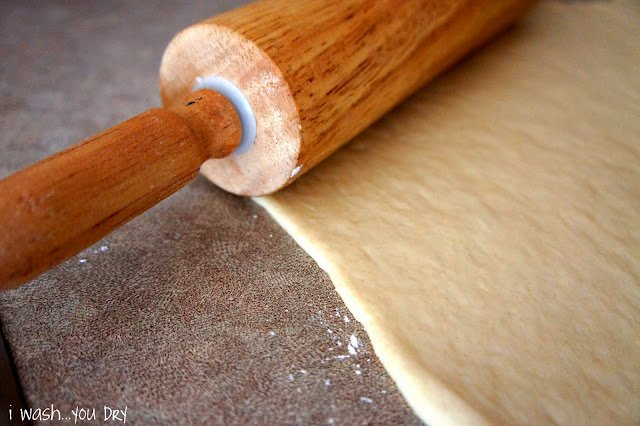 A rolling pin flattening dough for cinnamon rolls