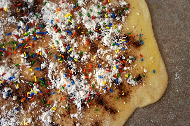 Flattened dough topped with cinnamon and sprinkles