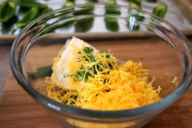 A glass bowl filled with cream cheese, shredded cheese and green onions