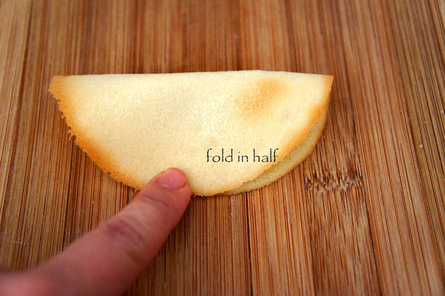 A finger demonstrating how to fold in half the baked fortune cookie dough to shape it