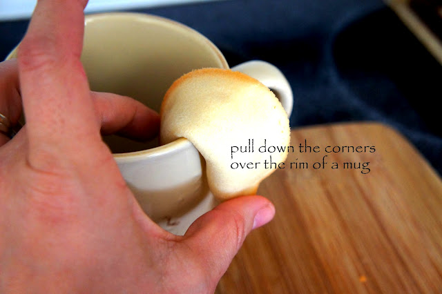 A hand demonstrating how to shape a fortune cookie using a mug