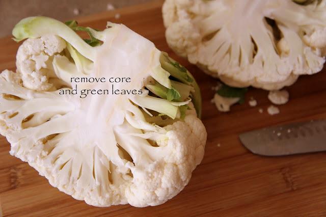 A close up of a cauliflower cut in half on a cutting board