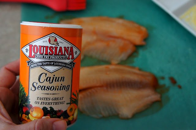 A hand holding a bottle of Louisiana Cajun Seasoning in front of a couple pieces of raw Tilapia
