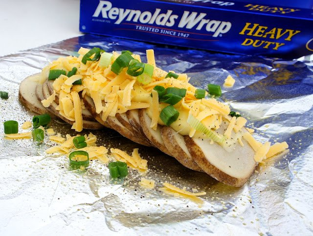 Sliced potatoes topped with shredded cheese and chives
