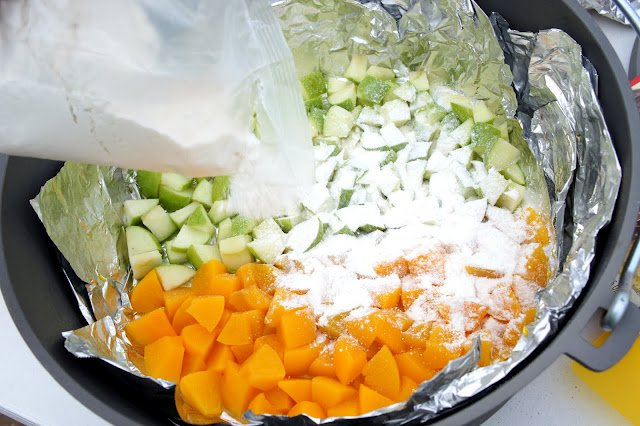 Cake mix powder being sprinkled over diced apples and peaches in a Dutch Oven.