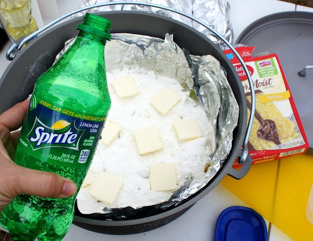 A hand holding a bottle of Sprite in front of a Dutch Oven filled with cobbler ingredients