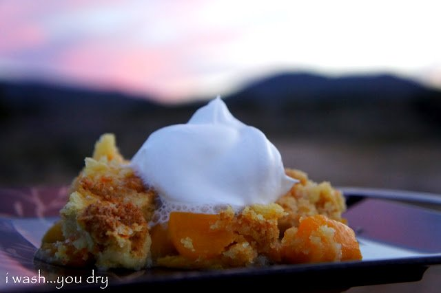 A close up of a peach cobbler topped with whipped cream