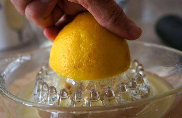 A hand juicing a lemon
