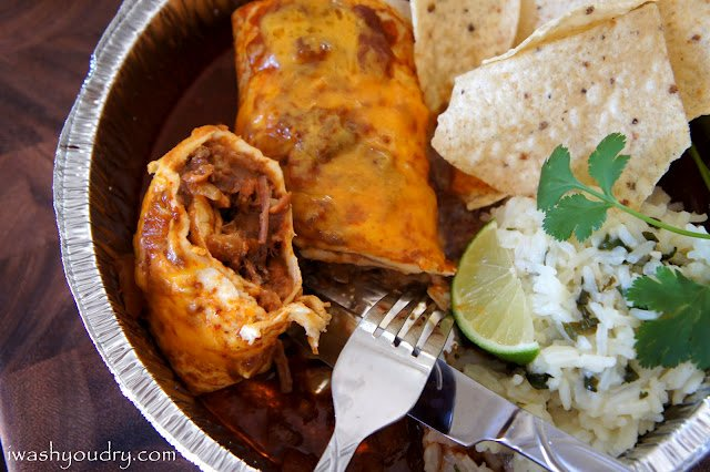 A close up of a smothered burrito cut in half in a tin dish with a side of chips and rice