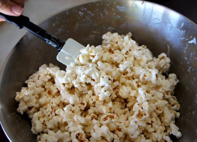 A spatula mixing a bowl of popcorn