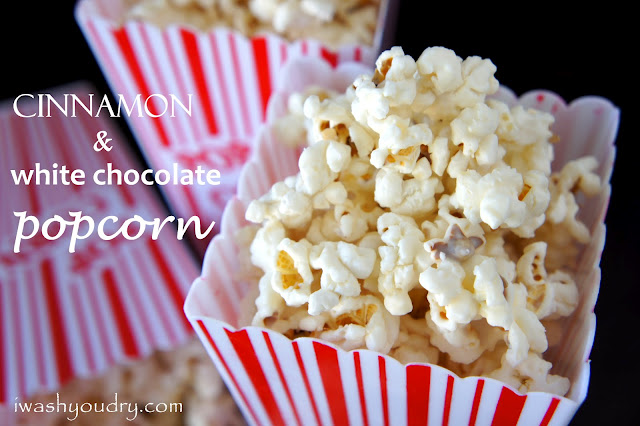 """Popcorn in a popcorn container and text next to it, \""""Cinnamon and White Chocolate Popcorn\"""""""