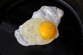 A close up of a fried egg in a skillet, sunny side up