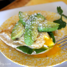 A plate with an Open Faced Egg and Avocado Sandwich on it