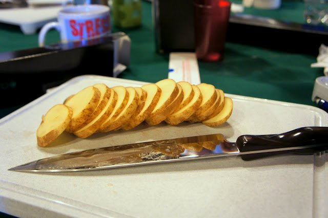 A cutting board with knife and sliced potatoes